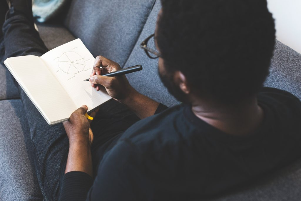 Photo of a Man Sketching Ideas in a Notebook